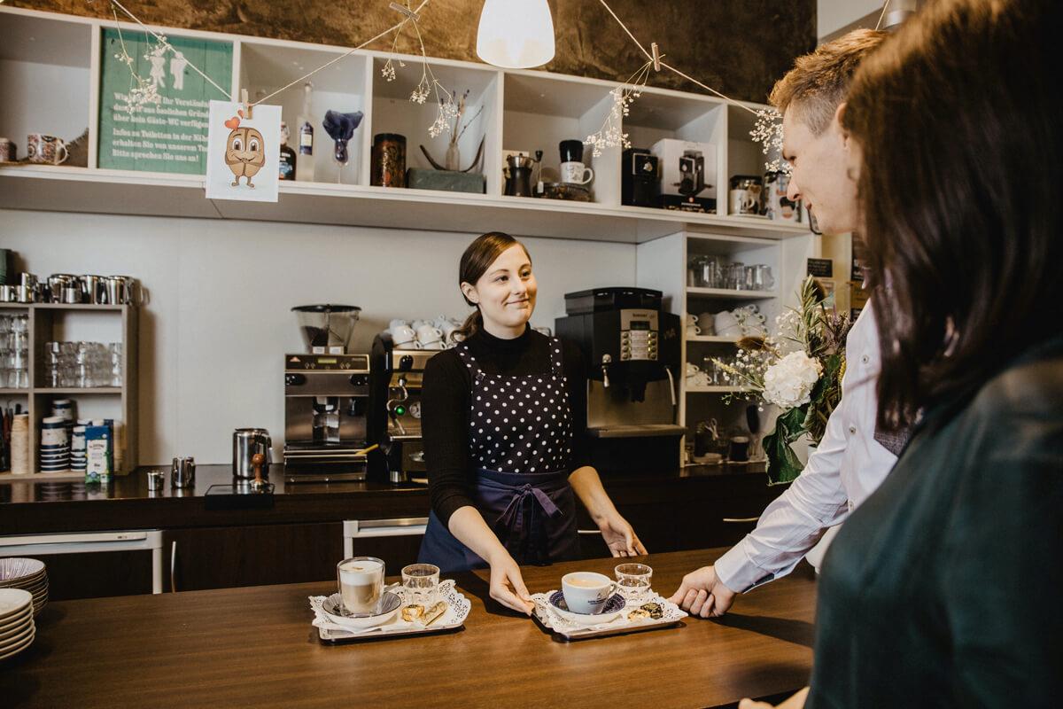 Eine Mitarbeiterin reicht Gästen ihre Getränke über die Cafébar.