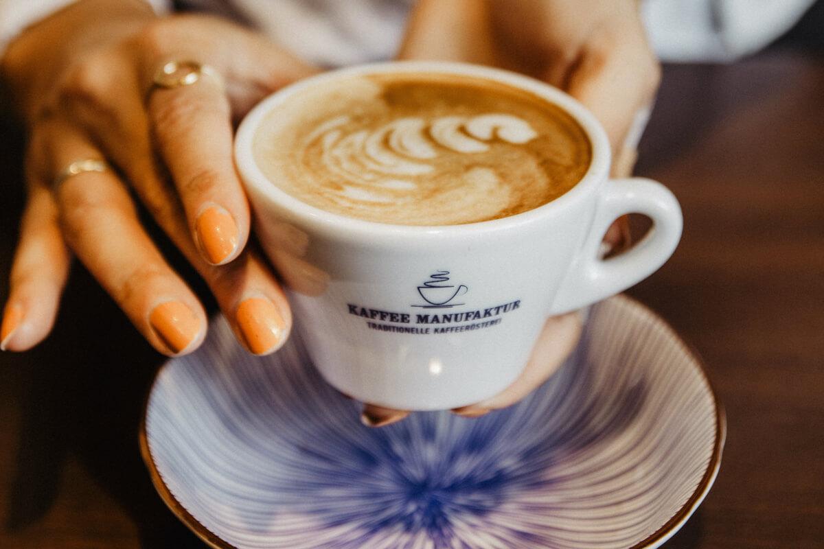 Eine Tasse Cappuccino wird dem Gast angerichtet.