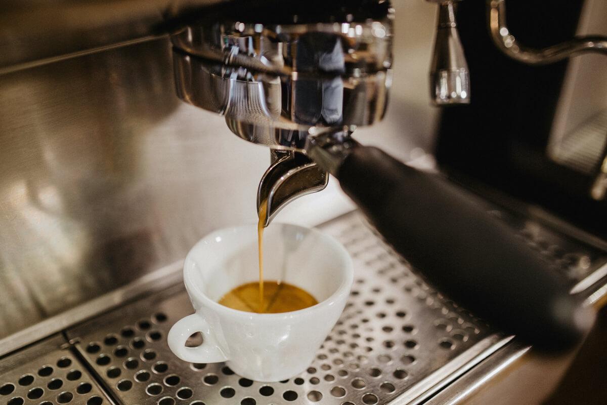 Nahaufnahme der Siebträgermaschine während frisch gebrühter Espresso in ein kleines Espresso-Tässchen fließt.