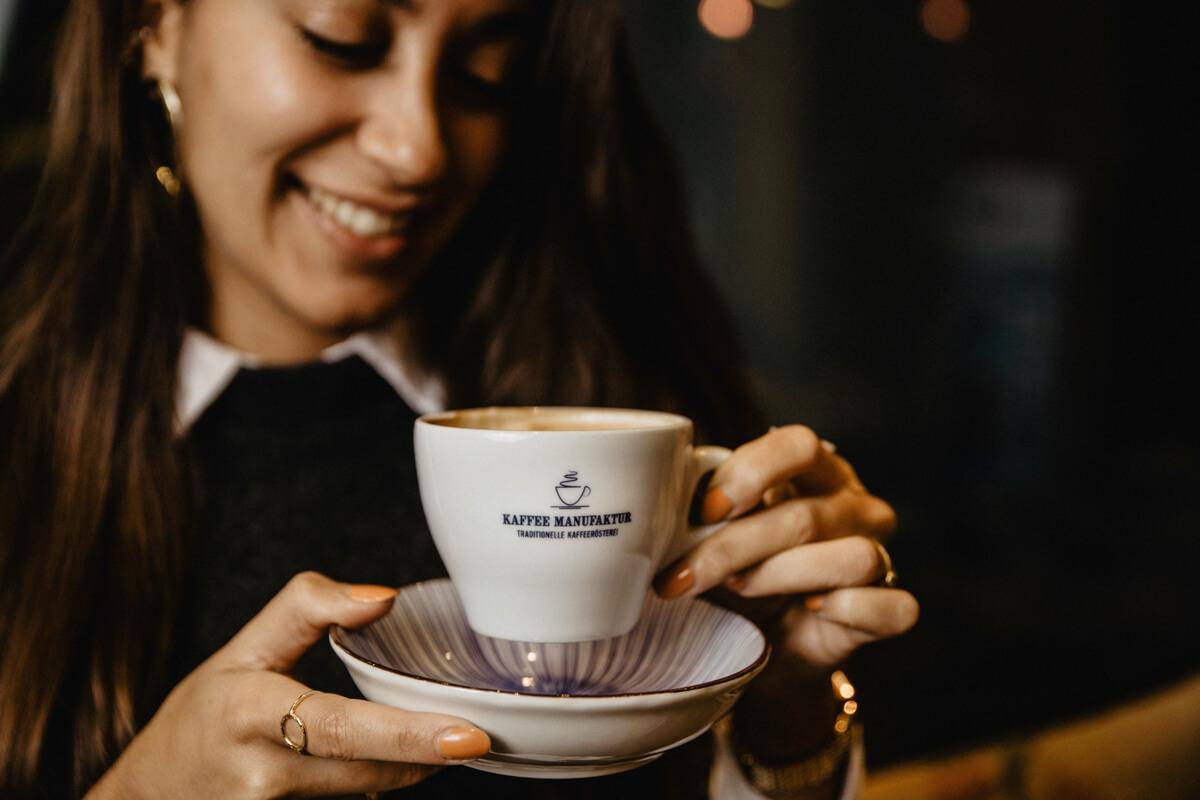 Eine junge Frau trinkt genüßlich einen Kaffee.