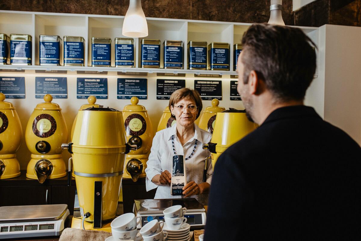 Die Inhaberin Andrea Werner berät einen Kunden bei der Kaffeeauswahl.
