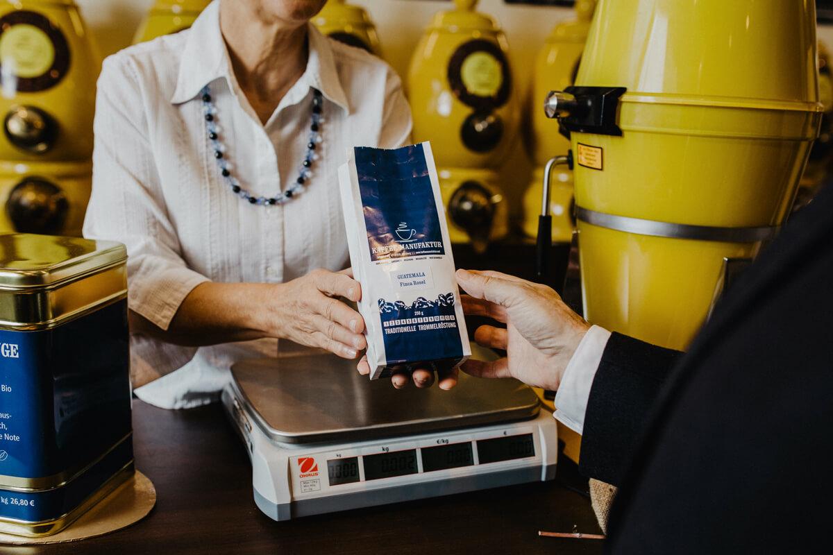 Eine Verkäuferin zeigt einem Kunden die Kaffeeverpackung.
