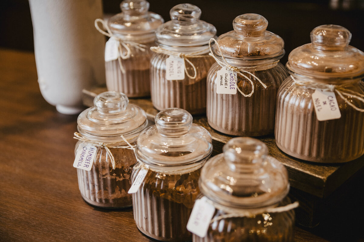 Gläser mit verschiedenen Kakaosorten stehen hübsch angerichtet auf dem Tresen.