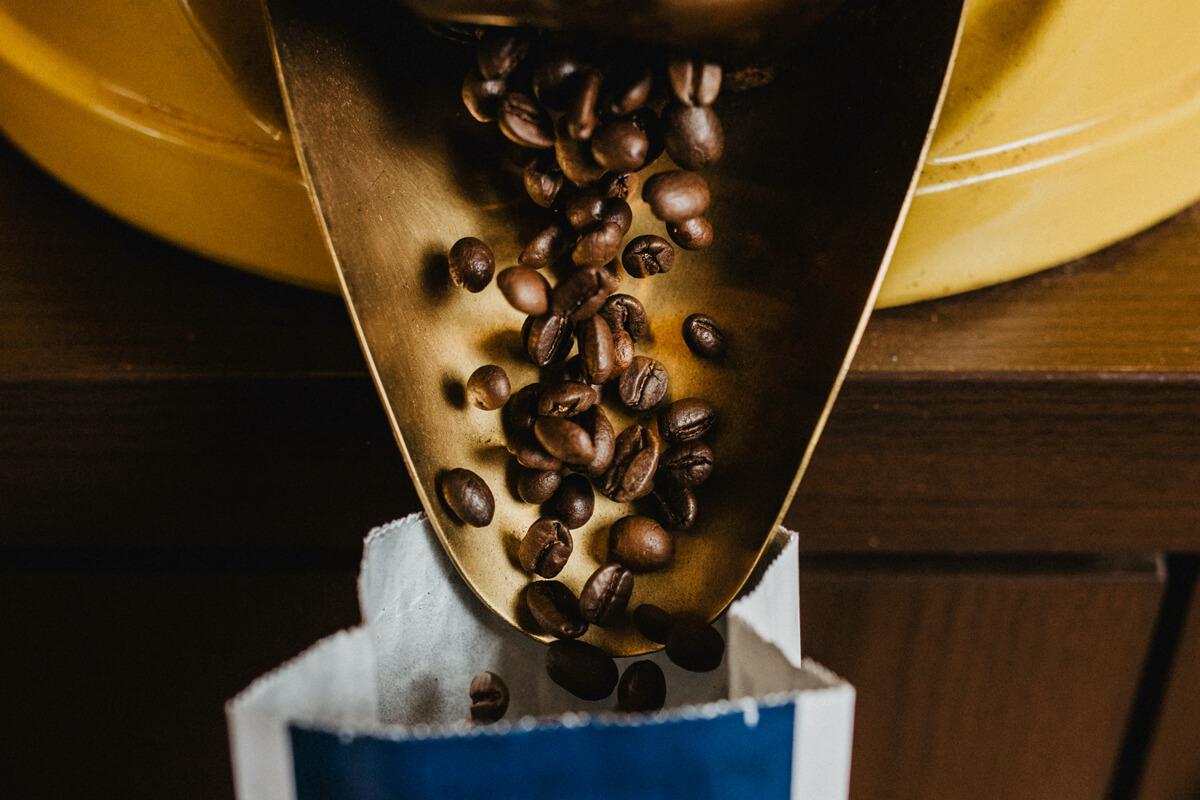 Kaffeebohnen fallen aus der Öffnung einer Kaffeeschütte in eine Aromatüte.Kaffeebohnen fallen aus der Öffnung einer Kaffeeschütte in eine Aromatüte.