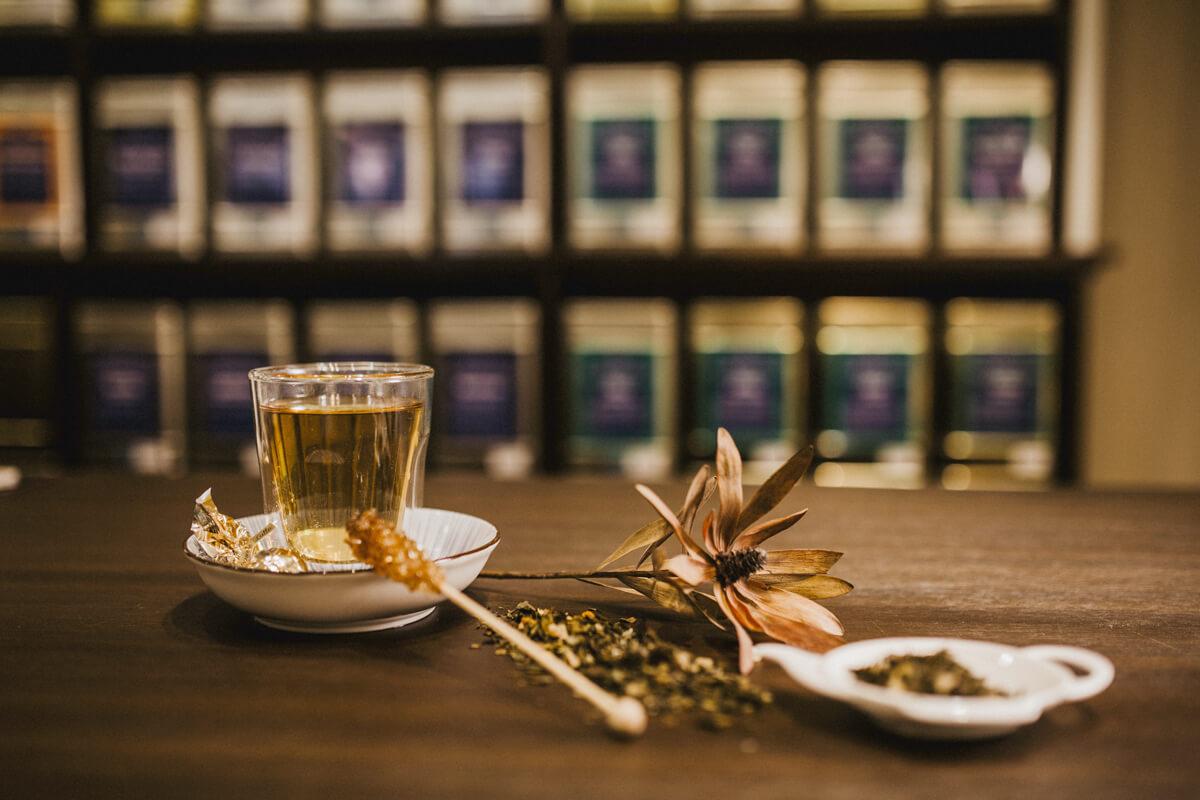 Ein Glas Tee steht schön angerichtet auf der Theke. In der Unschärfe im Hintergrund sind Teedosen erkennbar.