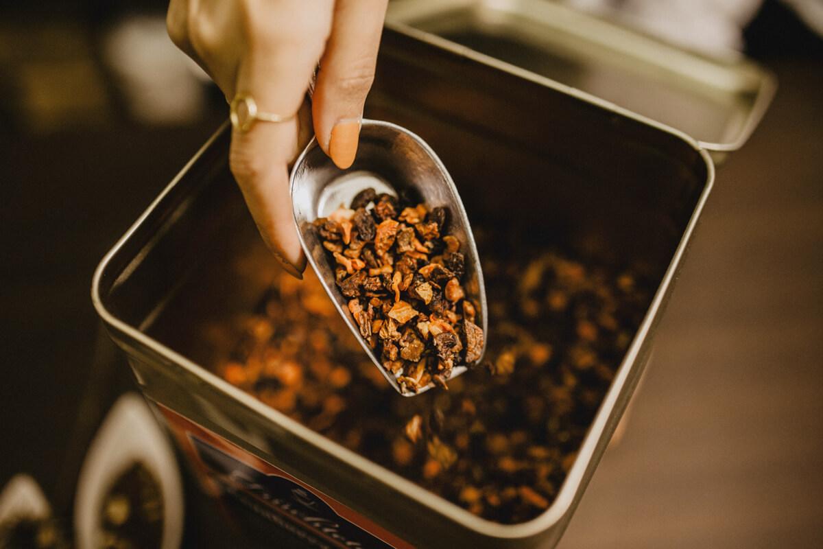 Früchtetee wird auf einer Kelle aus einer Teedose geschöpft.