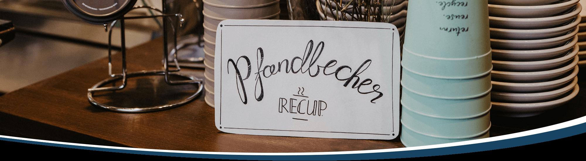 Ein kunstvoll geschriebenes Schild weist auf die Mehrweg-Pfadbecher von ReCup hin, die Gäste in der Kaffee Manufaktur erwerben können.