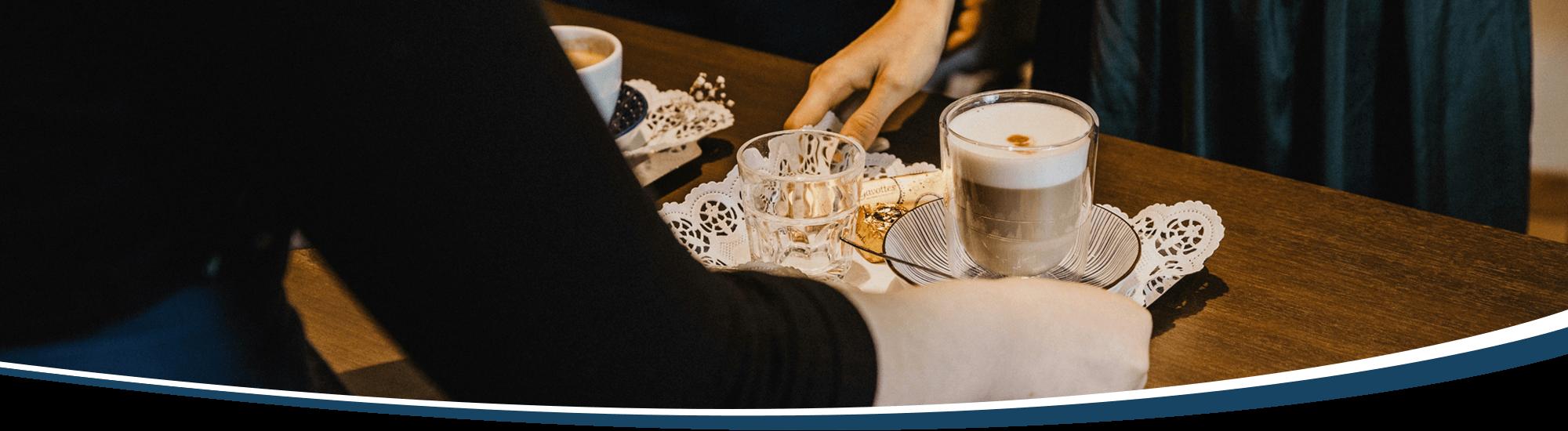 Eine Barista reicht Gästen ihre Getränke über die Cafébar.