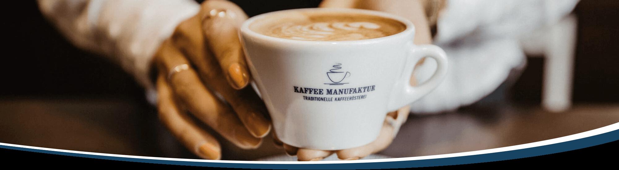 Eine Tasse Cappuccino wird von einer Barista über die Cafébar gereich