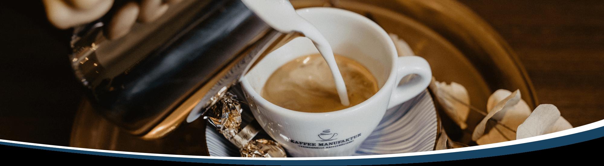 Cappuccinozubereitung: Eine Barista gibt den Milchschaum zum Espresso in die Cappuccinotasse und malt eine Blume in den Milchschaum.
