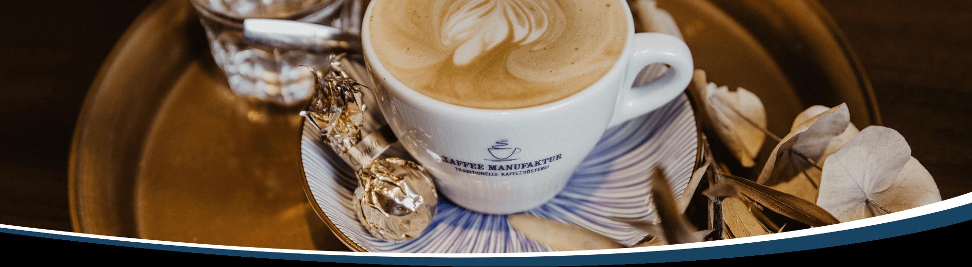 Eine Tasse Cappuccino und ein Glas Wasser sind sehr anstrechend und dekorativ auf einem Tablett angerichtet
