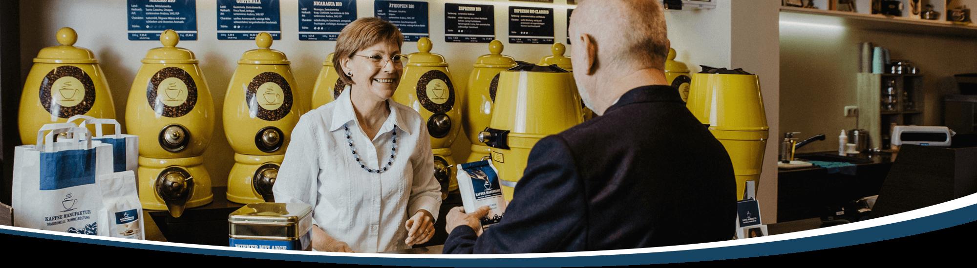 Die Inhaberin Andrea Werner übergibt einem Kunden seinen frisch gemahlenen Kaffee.