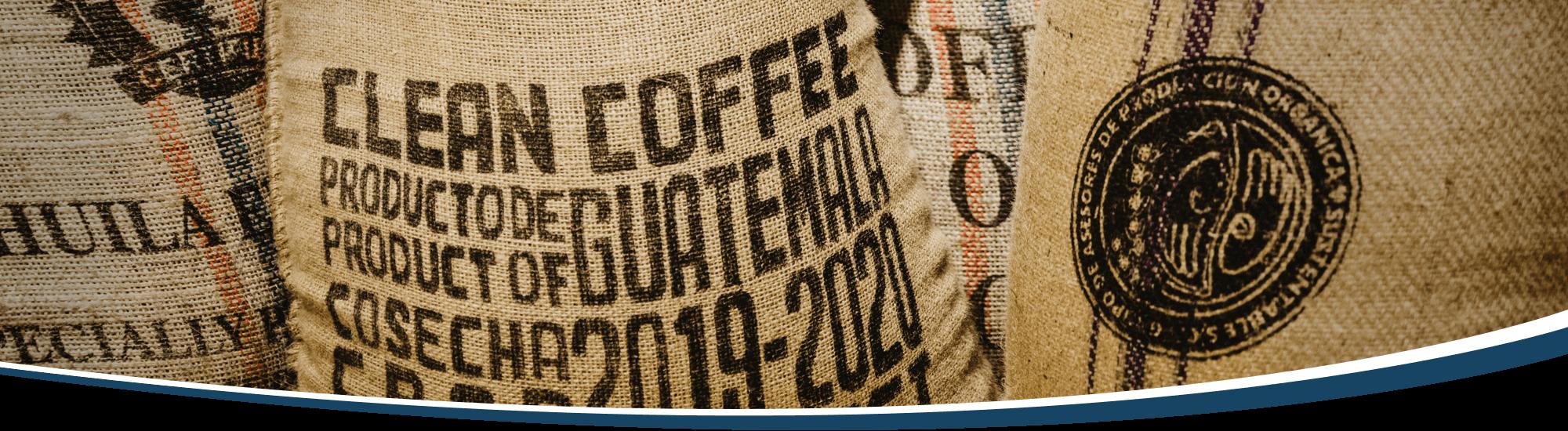Vielseitig bedruckte Kaffeesäcke aus Ländern rund um den Globus, stehen eng gedrungen beieinander.