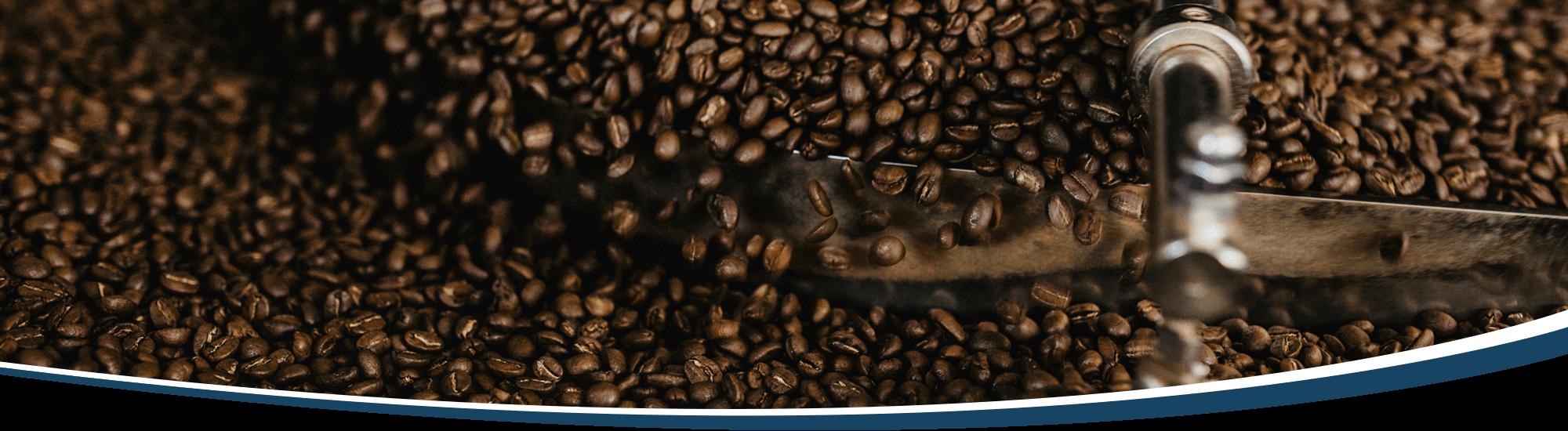 Frisch gerösteter Kaffee wird im Kühlsieb in Bewegung gehalten, während er auf Zimmertemperatur herunterkühlt.