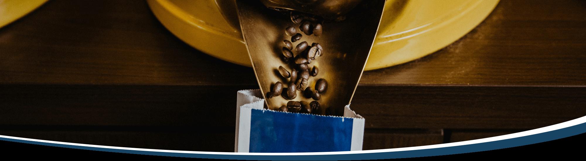 Kaffeebohnen fallen aus der Öffnung einer Kaffeeschütte in eine Aromatüte.