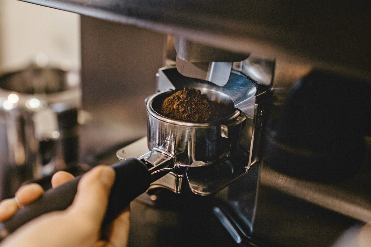 Für die Zubereitung eines Espressos wird Kaffee frisch in der Mühle gemahlen.