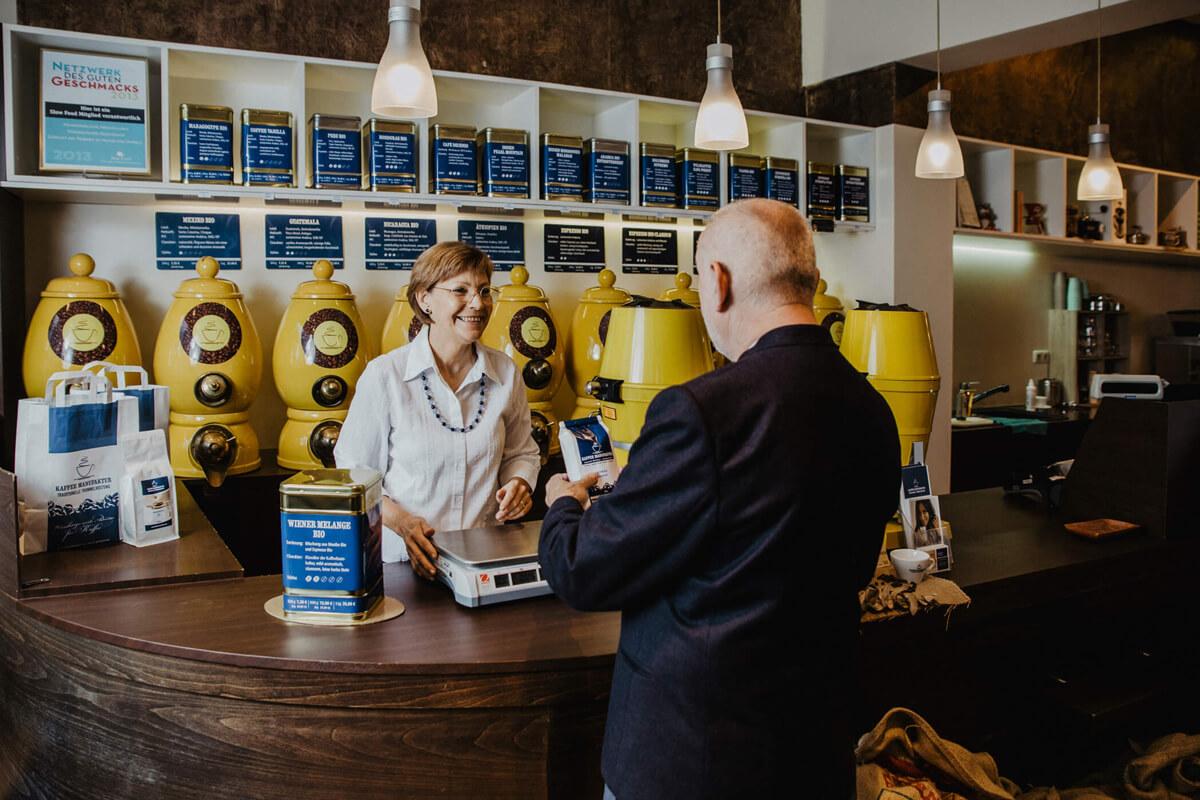 Ein Kunde kauft Kaffee am Verkaufstresen