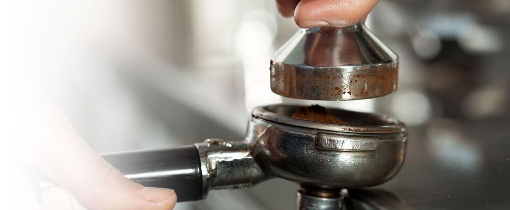 Espressozubereitung an einer Siebträgermaschine. Der Vorgang des Tampen wird gezeigt.