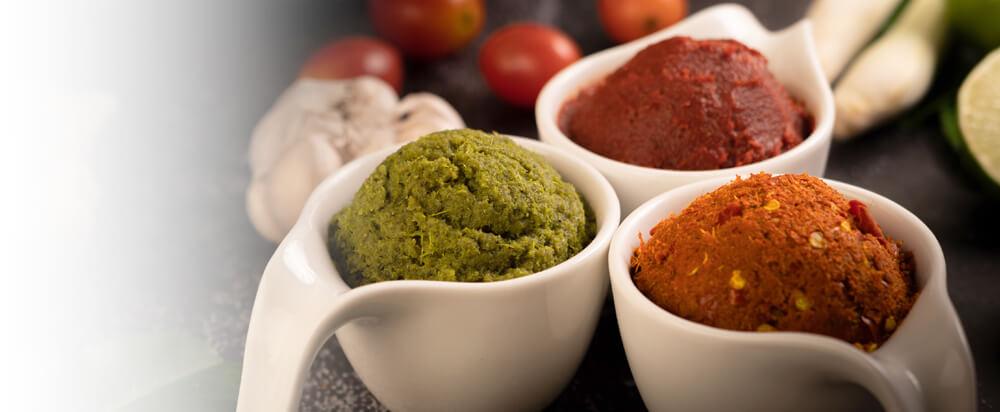 Drei Schälchen mit feinen Gewürzpasten stehen arrangiert nebeneinander und umgeben von vielem frischen Gemüse