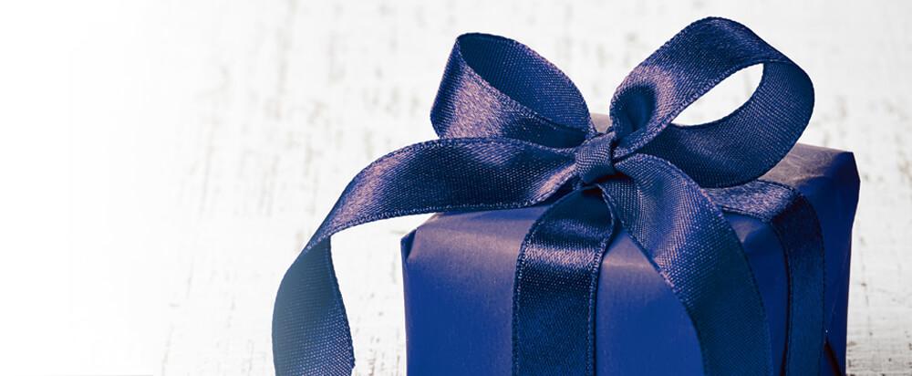 Attraktiv verpacktes Geschenk in blauem Geschenkpapier mit einer üppigen Schleife aus hochwertigem Satinband