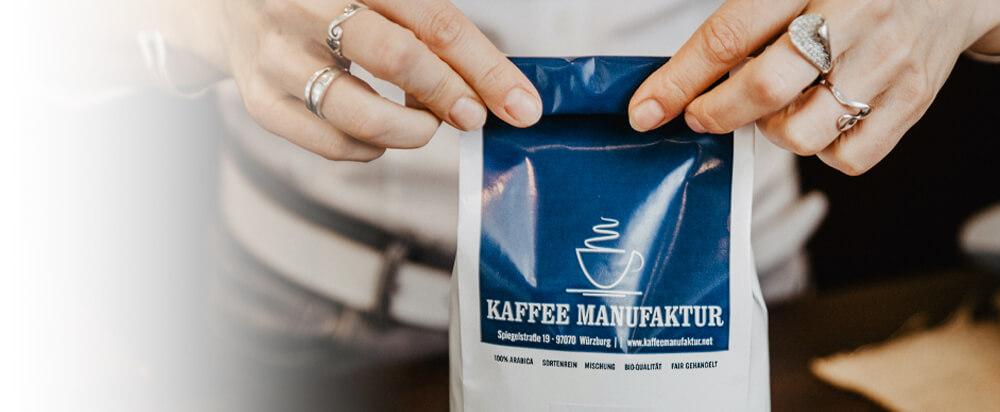 Eine Tüte Kaffee wird von Hand verschlossen