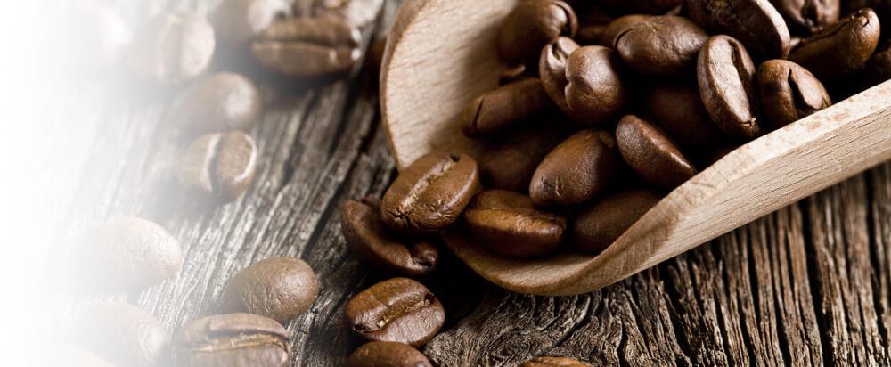Kaffeebohnen liegen hübsch drapiert auf einer Schöpfkelle aus Holz