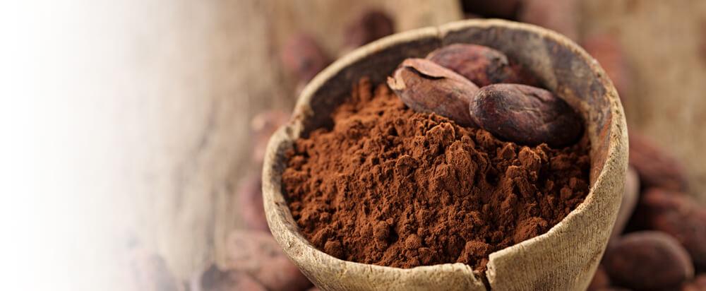 Frisch gemahlenes Kakaopulver ist dekorativ in einer rustikalen Schöpfkelle aus Holz angerichtet