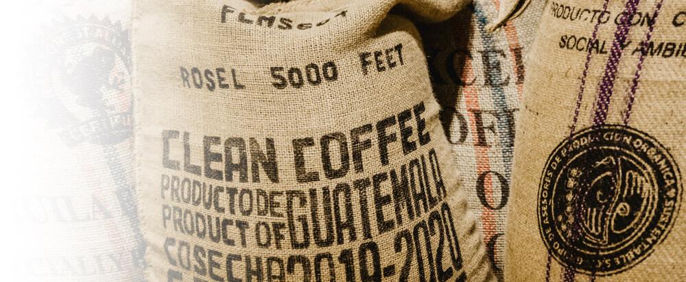 Kaffeesäcke voll Rohbohnen stehen eng gedrungen nebeneinander