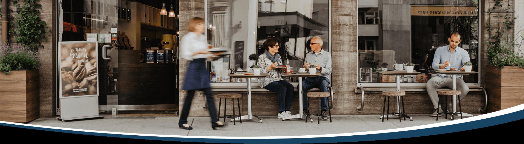 Vor der Kaffeerösterei sitzen Gäste und trinken Kaffee